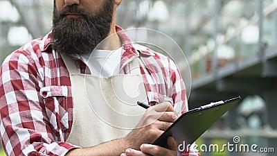 Rolnik płci męskiej piszący notatki z raportu w schowku przez długopis, pracownik wsi, botanika zbiory wideo