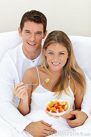 Romaantic couple eating fruit lying on their bed