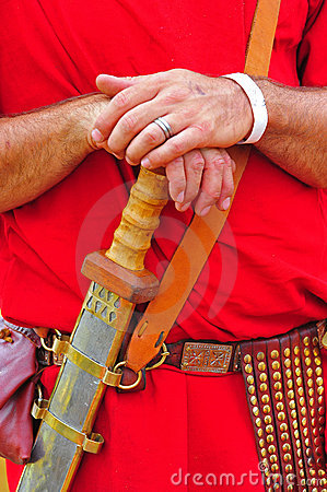 A roman soldier rests his hands on his sword
