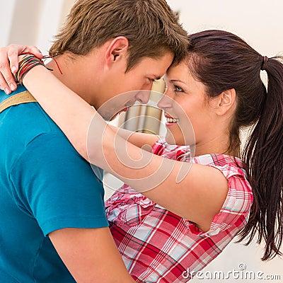 Romance de abarcamiento y sonriente de los pares cariñosos jovenes