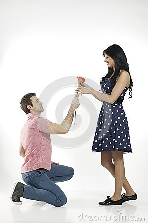 Romantic boy giving rose to his girlfriend