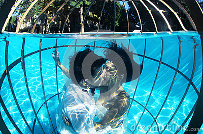 Romantic bride and groom underwater in a bird cage