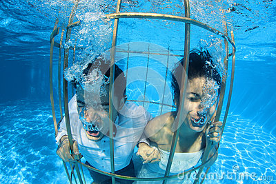 Romantic bride and groom underwater in a bird cage
