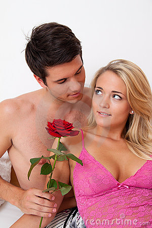 Romantic couple in bed with Rose. Marry the man.