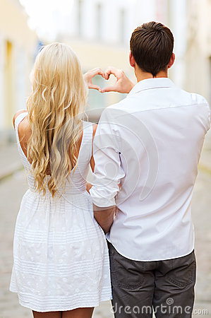 Romantic couple in the city making heart shape