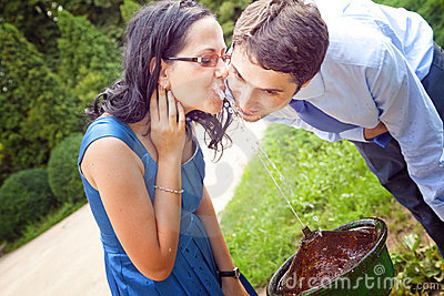 Romantic couple drinking water from park fountain