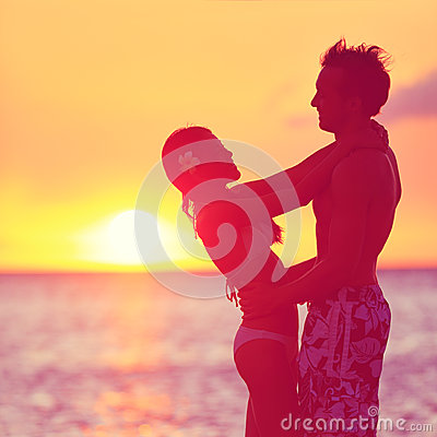 Romantic couple embracing kissing on beach sunset