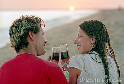 Romantic couple with goblet of wine on a beach