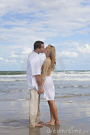 Romantic Couple Holding Hands & Kissing On A Beach
