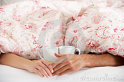 Romantic Couple Holding Hands Under Duvet In Bed