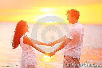 Romantic couple lovers holding hands, beach sunset