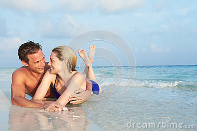 Romantic Couple Lying In Sea On Tropical Beach Holiday