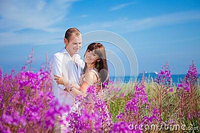 Romantic couple among purple flowers near blue sea