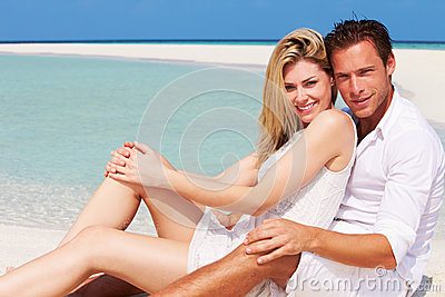 Romantic Couple Sitting On Beautiful Tropical Beach