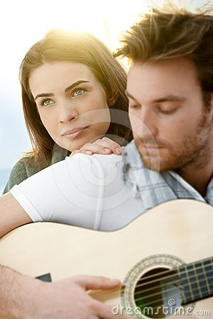 Romantic couple sitting playing guitar outdoor �