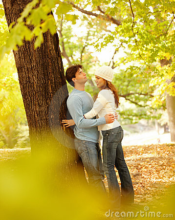 Romantic couple standing by  tree hugging