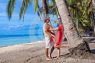 Romantic couple at tropical beach near palm tree