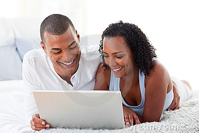 Romantic couple using a laptop at home