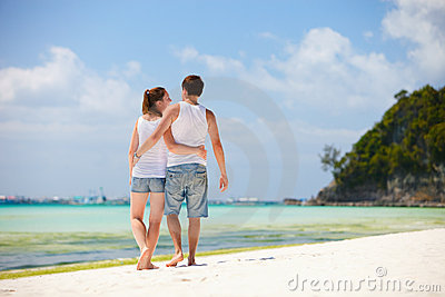 Romantic couple walking along tropical beach
