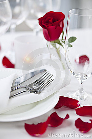 Romantic dinner setting with rose petals