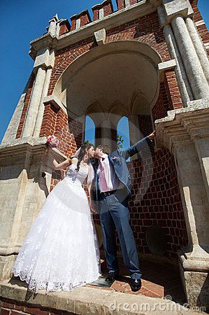 Romantic kiss bride and groom and ancient building