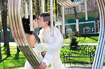Romantic kiss bride and groom about art ironwork