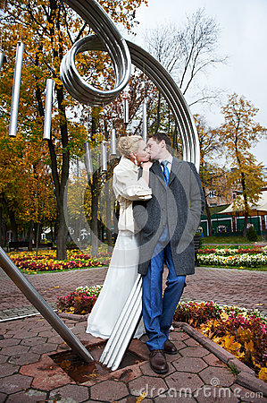 Romantic kiss bride and groom in autumn park