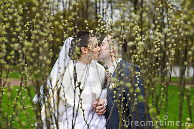 Romantic kiss bride and groom in park