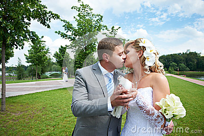Romantic kiss bride and groom with pigeons in park