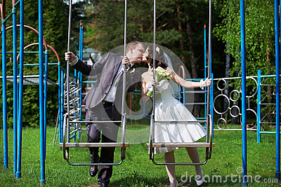 Romantic kiss bride and groom on swing