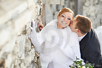 Romantic kiss happy bride and groom on wedding day