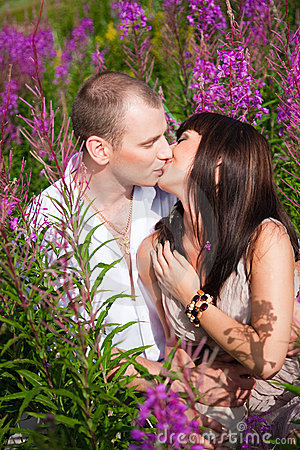 Romantic kiss among purple flowers