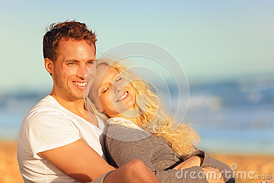 Romantic lovers relaxing at sunset beach
