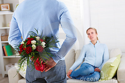 Romantic man hiding roses behind his back