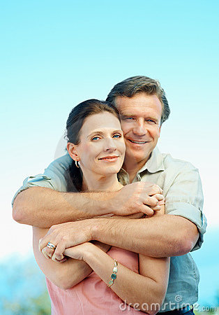 Romantic Mature Couple Embracing Against Blue Sky Royalty Free Stock Image - Image: 12411856