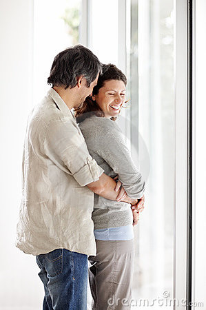 Romantic mature couple embracing near a window