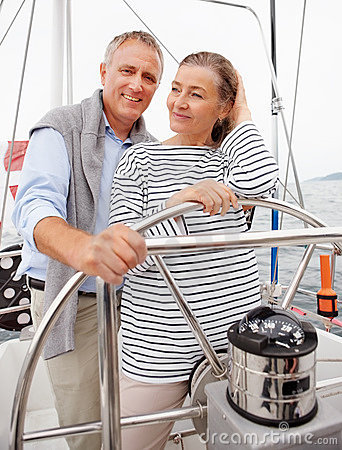 Romantic mature couple steering the boat