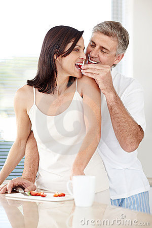 Romantic mature man feeding fruits to his wife