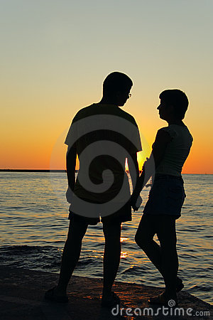 Romantic pair looking at each other at sunset