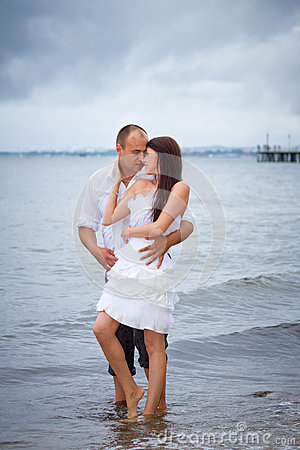 Romantic pose of married couple at the sea