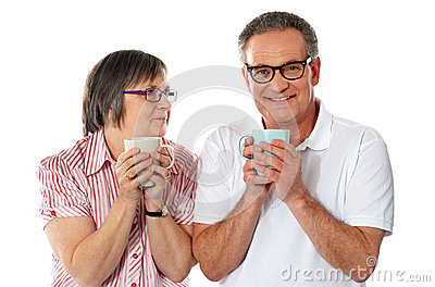 Romantic senior couple holding coffee mugs