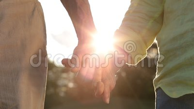 Romantic senior couple holding hands at sunset stock video