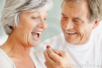 Romantic senior man giving a grape to a cute woman