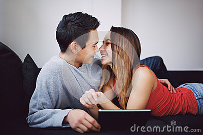 Romantic teenage couple on couch with tablet