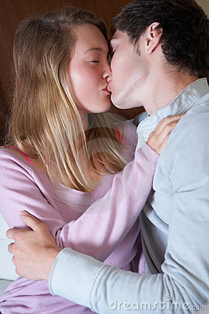 Romantic Teenage Couple Kissing On Sofa At Home