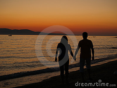 Romantic walk on the beach at sunset.