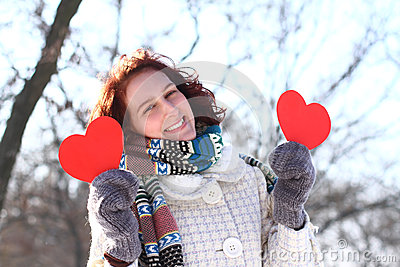 Romantic winter girl with two red hearts outdoors