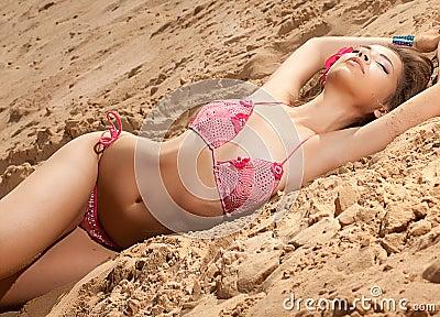 Romantic woman in bikini on sand sunbathing
