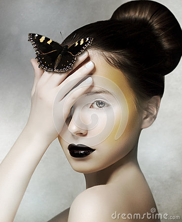 Romantic Woman holding Butterfly in her Hand. Fantasy Stock Photo