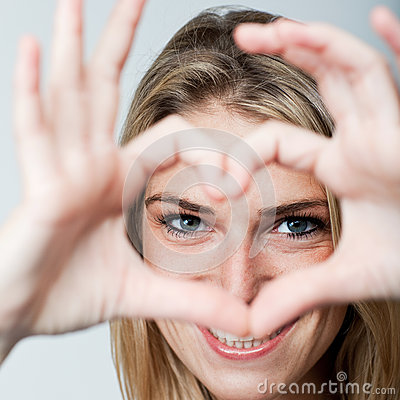 Romantic woman making a heart gesture